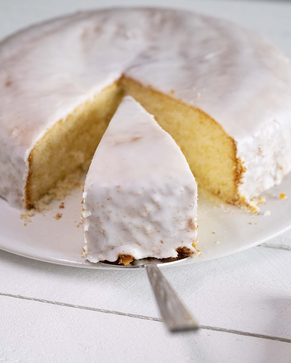 Nachaufnahme auf den ganzen Kuchen. Mit einem Kuchenheber heben wir gleich das angeschnittene Stück Zitronenkuchen hinaus.