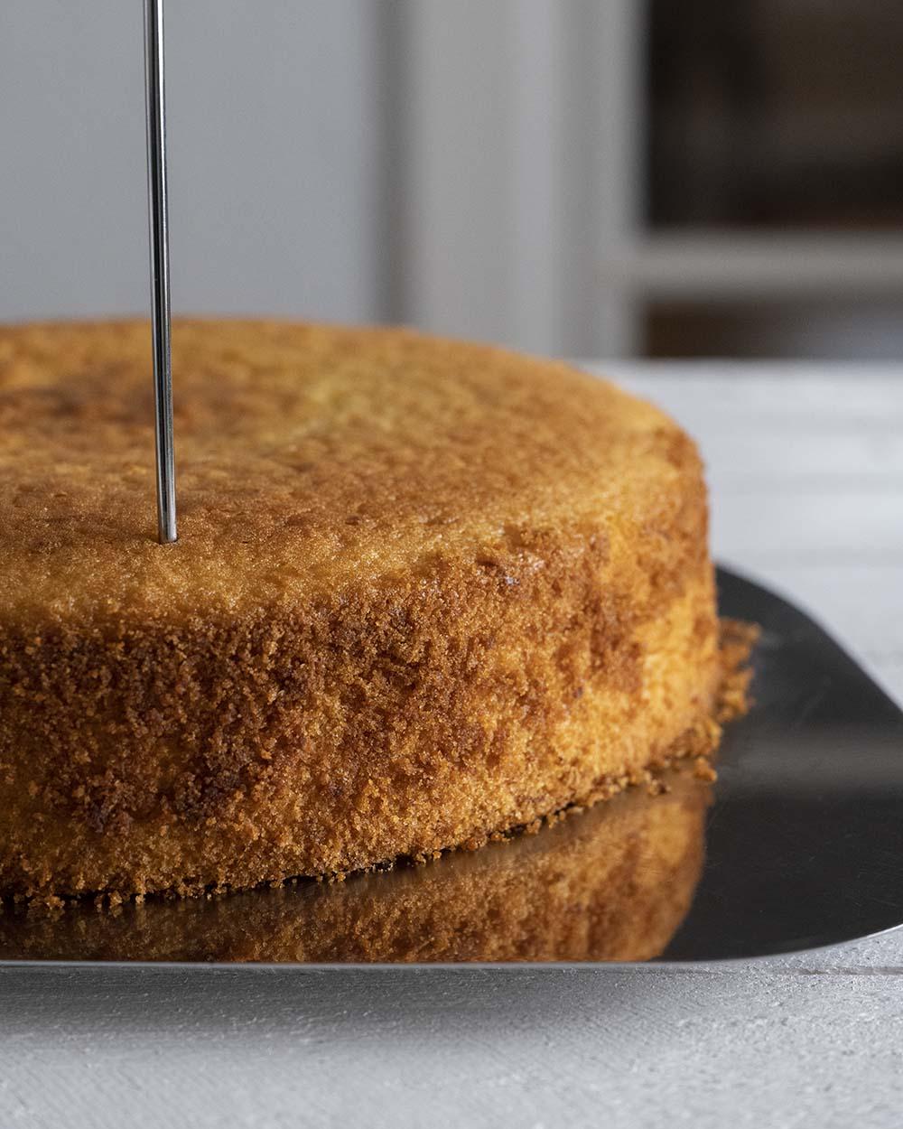 Wir stechen unseren Zitronenkuchen nach dem Backen mit einem Spieß ein. Er bekommt Löcher, damit später der Guss in den Kuchen fließt.