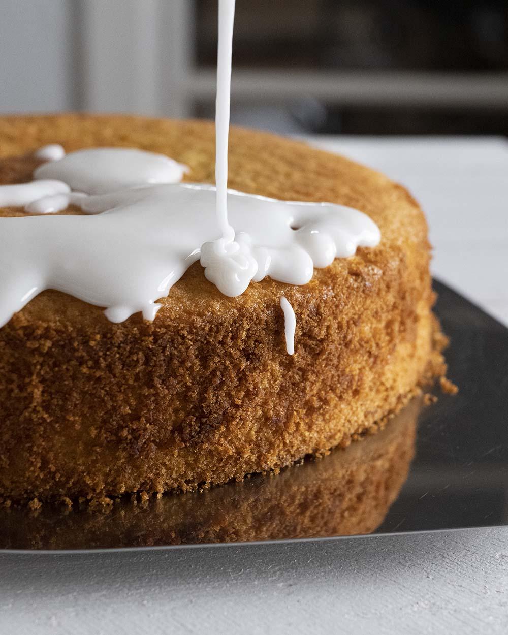 Unser selbst gemachter Zitronenguss fließt auf den frisch gebackenen Zitronenkuchen.