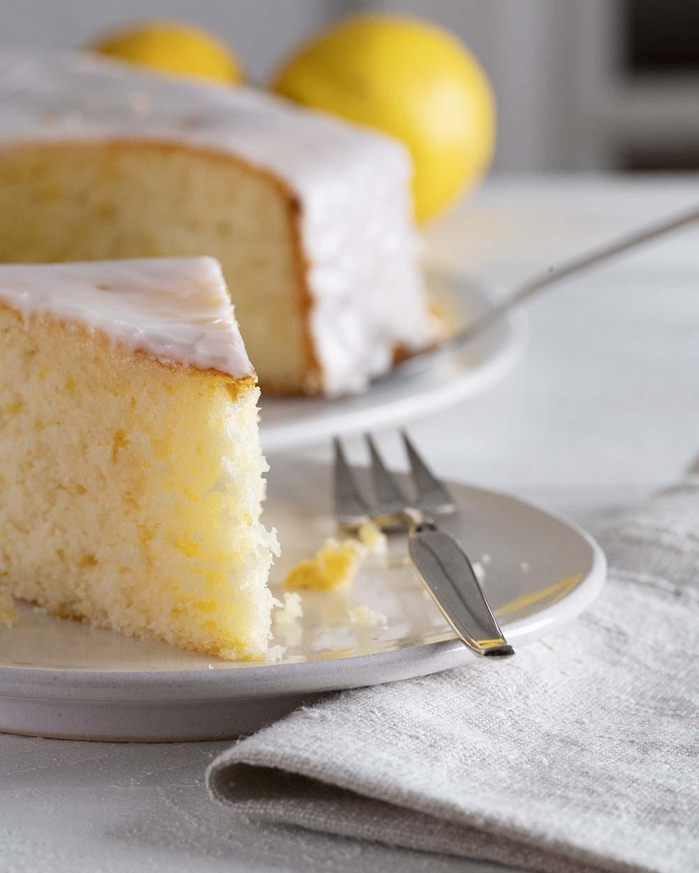 Im Vordergrund ist ein Stück Zitronenkuchen zu sehen. Auf die Spitze fällt Licht und zeigt die schöne gelbe Farbe.