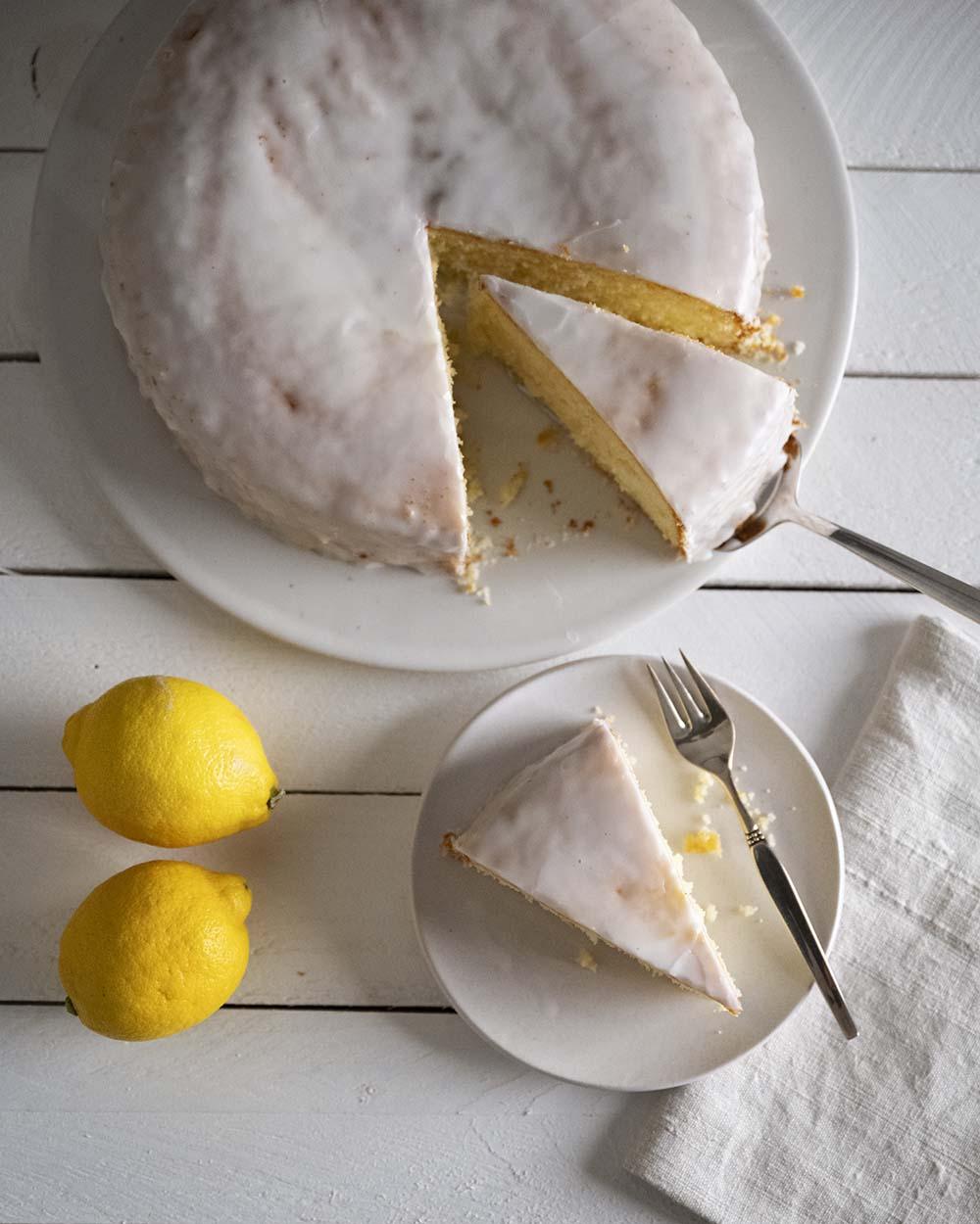 Wir haben unseren saftigen Zitronenkuchen angeschnitten und ein Stück auf einen Teller gehoben.