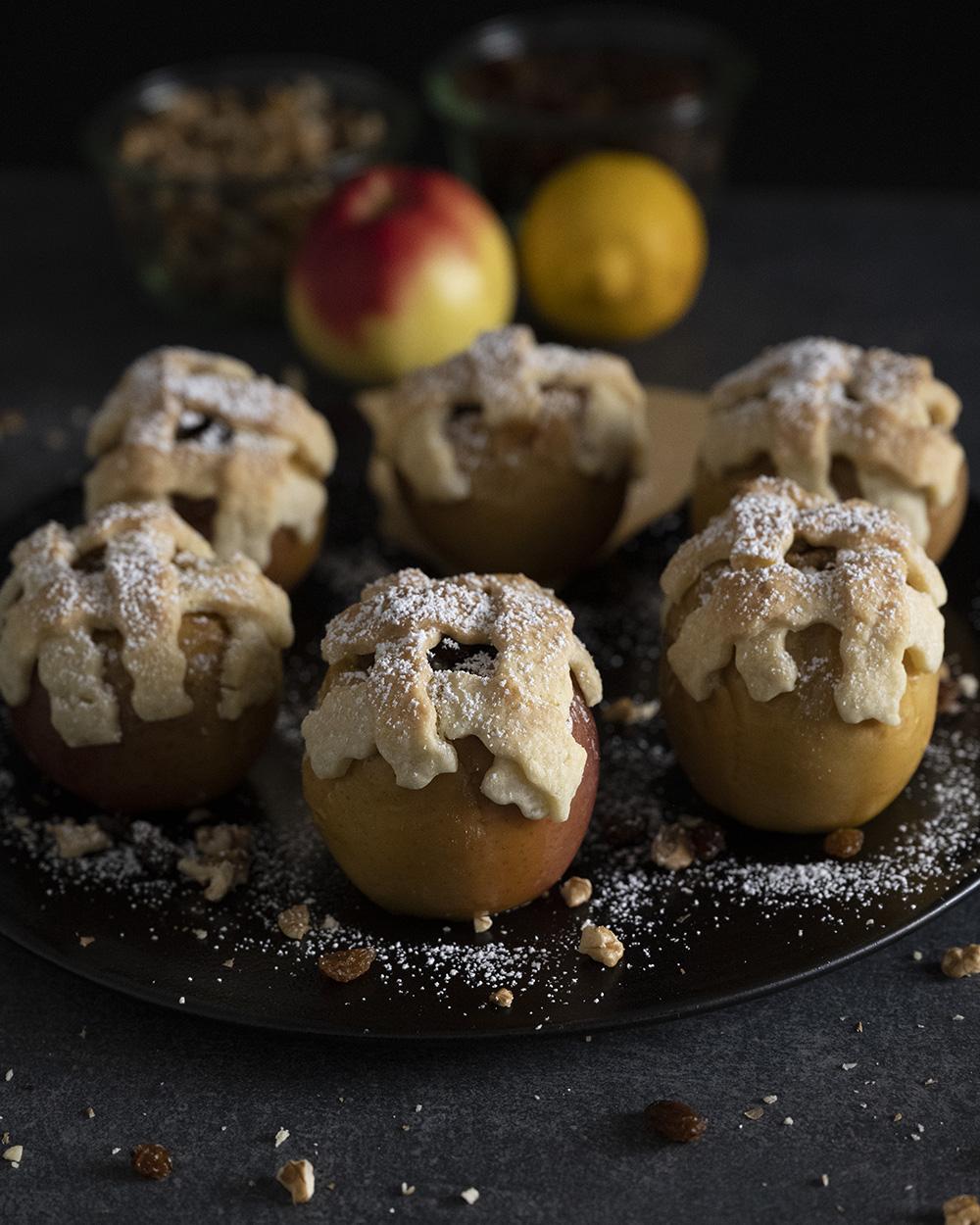 Sechs Bratäpfel sind auf einem Teller angerichtet und mit Puderzucker verziert.