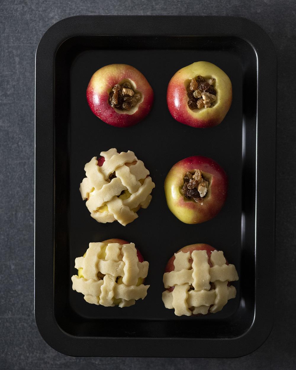 Sechs Äpfel liegen vor dem Backen in einer Backform. Drei tragen bereits eine Haube aus Mürbeteig.