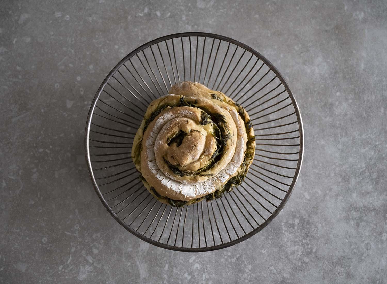 Eine fertig gebackene Brot-Schnecke mit Salat liegt in einem Brotkörbchen.