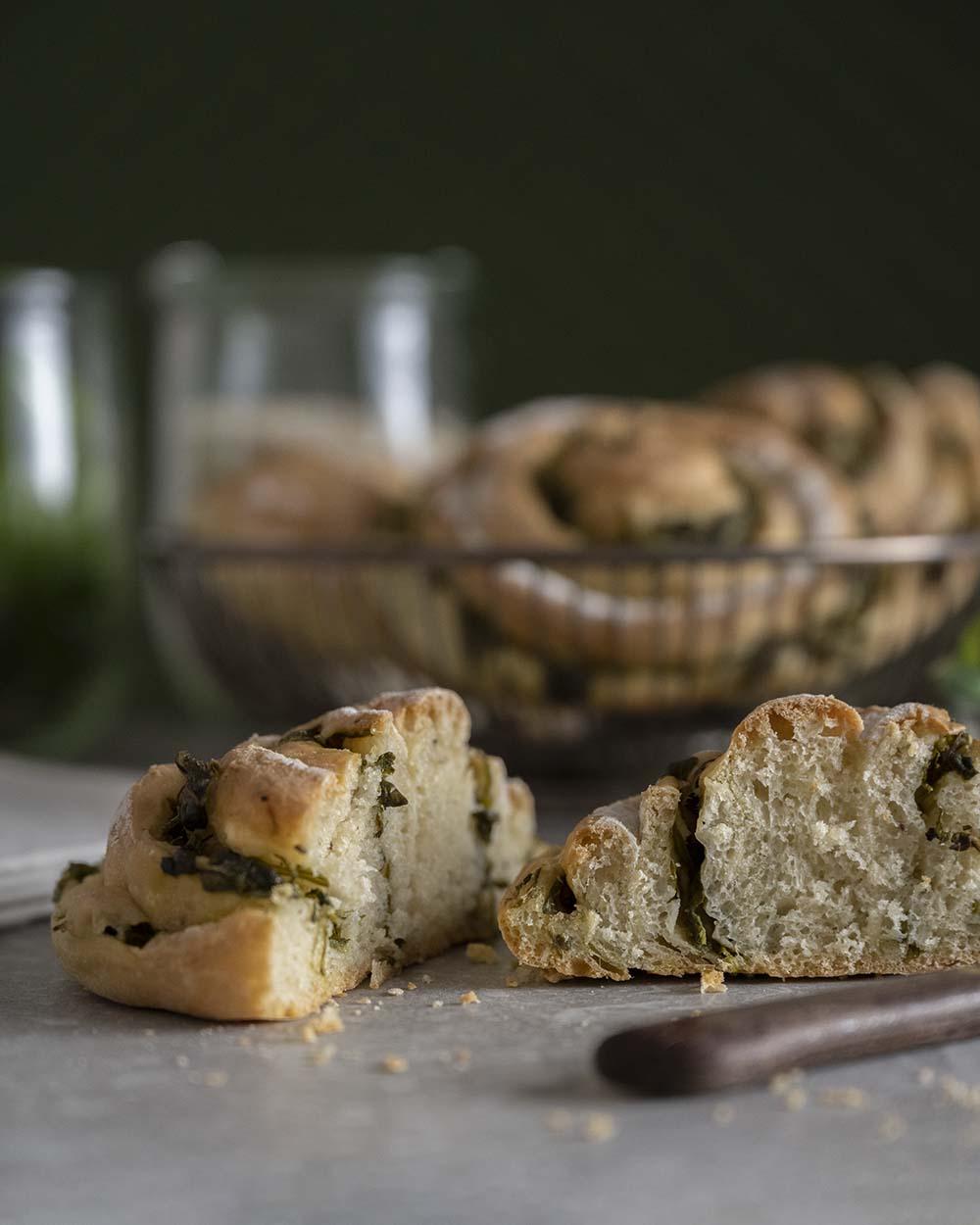 Wir haben eine Brot-Schnecke in der Mitte durchgeschnitten. Zu sehen ist die Porung und die Füllung aus Salat, die sich durch das Gebäck zieht.