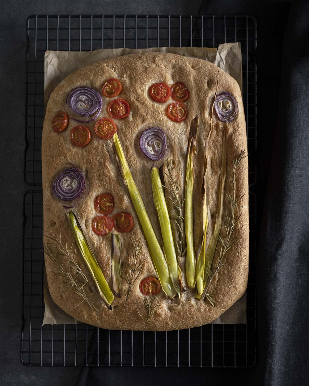 Frisch aus dem Ofen kühlt das Focaccia mit Gemüse auf einem Auskühlgitter aus.