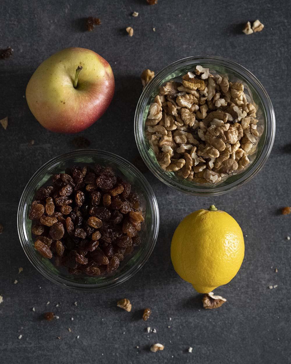 Zutaten für unseren Bratapfel auf einen Blick, darunter der Apfel, eine Zitrone, Rosinen und Walnüsse.