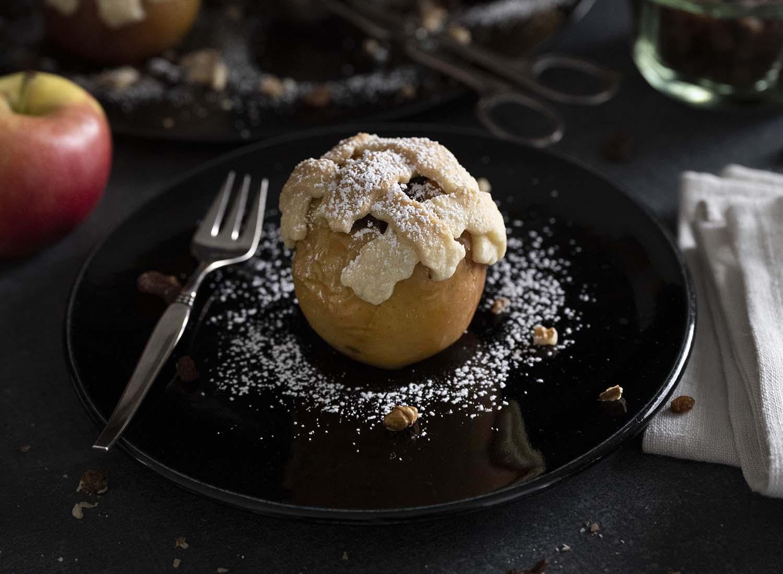 Wir haben einen Bratapfel mit Mürbeteighaube auf einem Teller angerichtet. Verziert haben wir ihn mit Puderzucker.