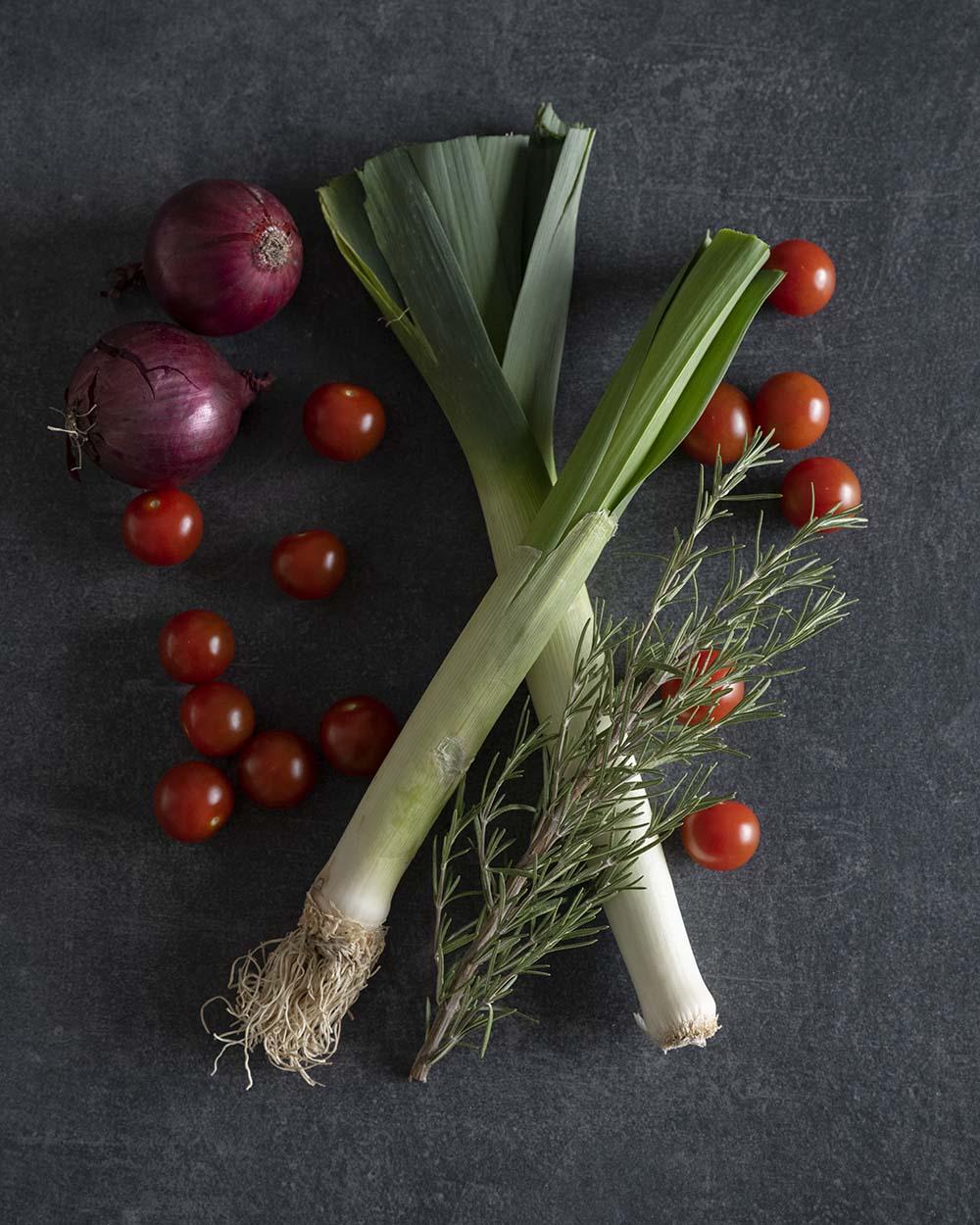 Gemüse für unser Focaccia mit Gemüse: Auf einer Fliese liegen Tomaten, rote Zwiebeln, zwei Stangen Lauch und ein großer Zweig Rosmarin.