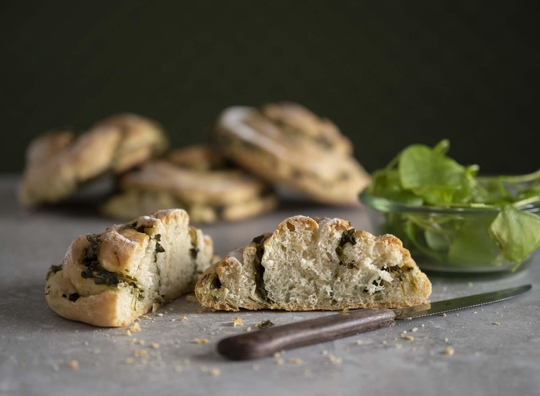 Wir haben eine unserer frisch gebackenen Brot-Schnecken mit Salat angeschnitten. Im Hintergrund sind weitere Schnecken zu sehen.