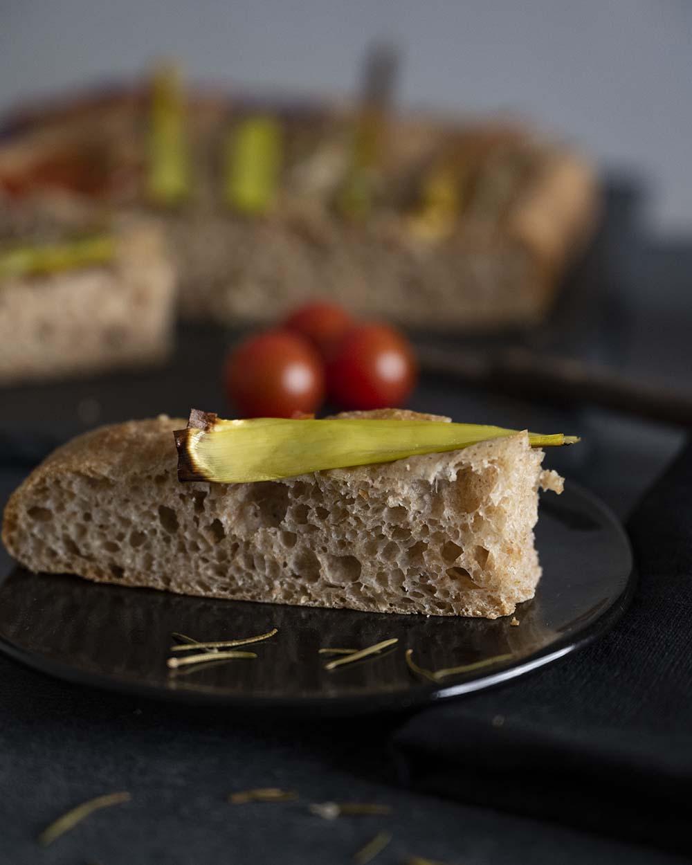 Ein Stück Foaccia mit gEmüse auf einem Teller. Auf der Scheibe Brot ist ein Stück Lauch zu sehen.
