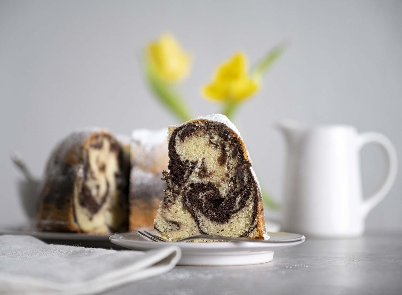 Ein Stück Marmorkuchen nach einem Rezept von der Oma, angerichtet auf einem Teller. Im Hintergrund ist der ganze Gugelhupf zu sehen.