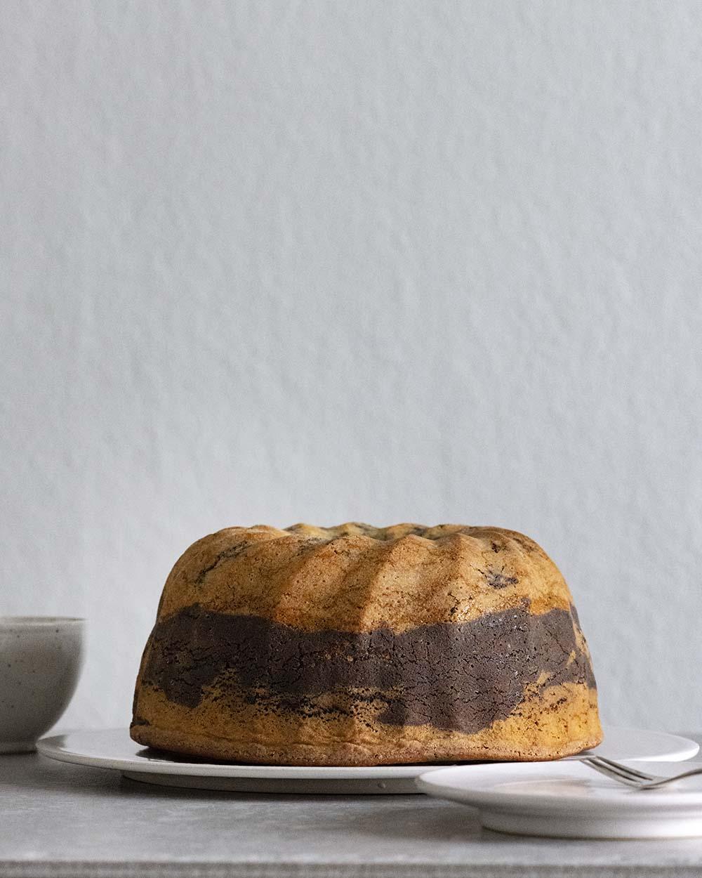 Wir haben den Marmorkuchen aus der Form gelöst. Er steht jetzt auf einer Kuchenplatte auf dem Tisch.