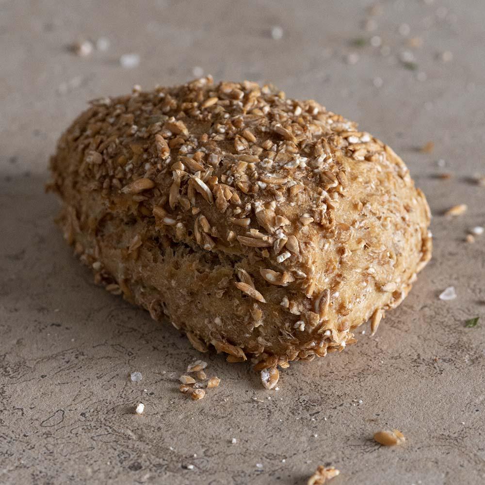 Einvollwertiges Brötchen mit Schrot in der Nahaufnahme: Dieses haben wir vor dem Backen in zusätzlich eingeweichtem Schrot gewälzt.