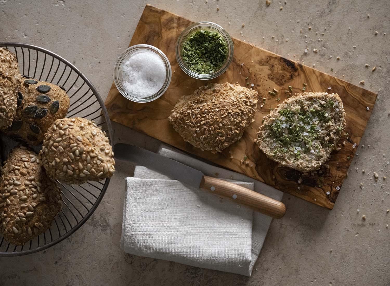 Ein vollwertiges Brötchen mit Schrot liegt aufgeschnitten auf einem Frühstücksbrett. Darauf haben wir Schnittlauch und Salzkörner gestreut.ot auf einem Frühstücksbrett.