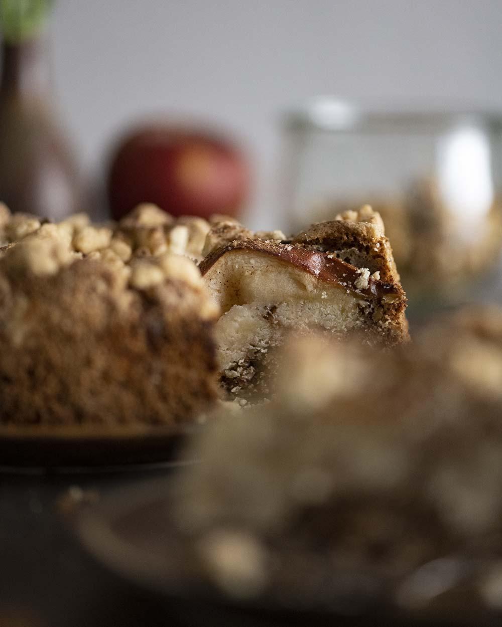 Wir haben auf die ganzen Äpfel fokussiert, die wir auf unseren Apfel Streusel Kuchen geben. Der Kuchen steht auf der Kaffeetafel und ist angeschnitten.