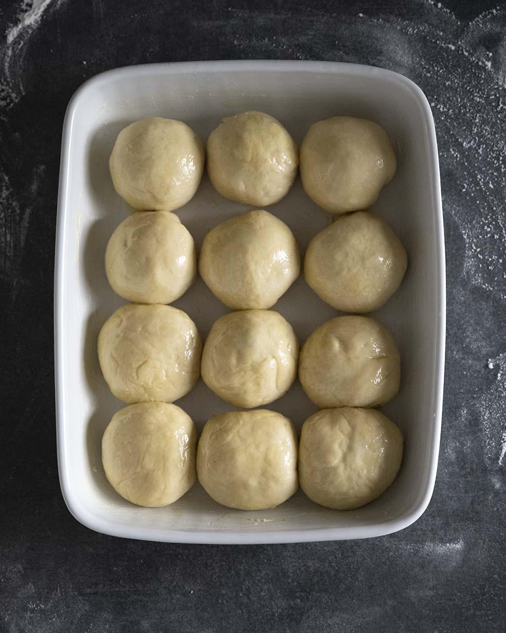 Wir haben die 12 Buchteln in eine Backform gelegt und mit Butter eingestrichen. Jetzt kommen sie in den Ofen.