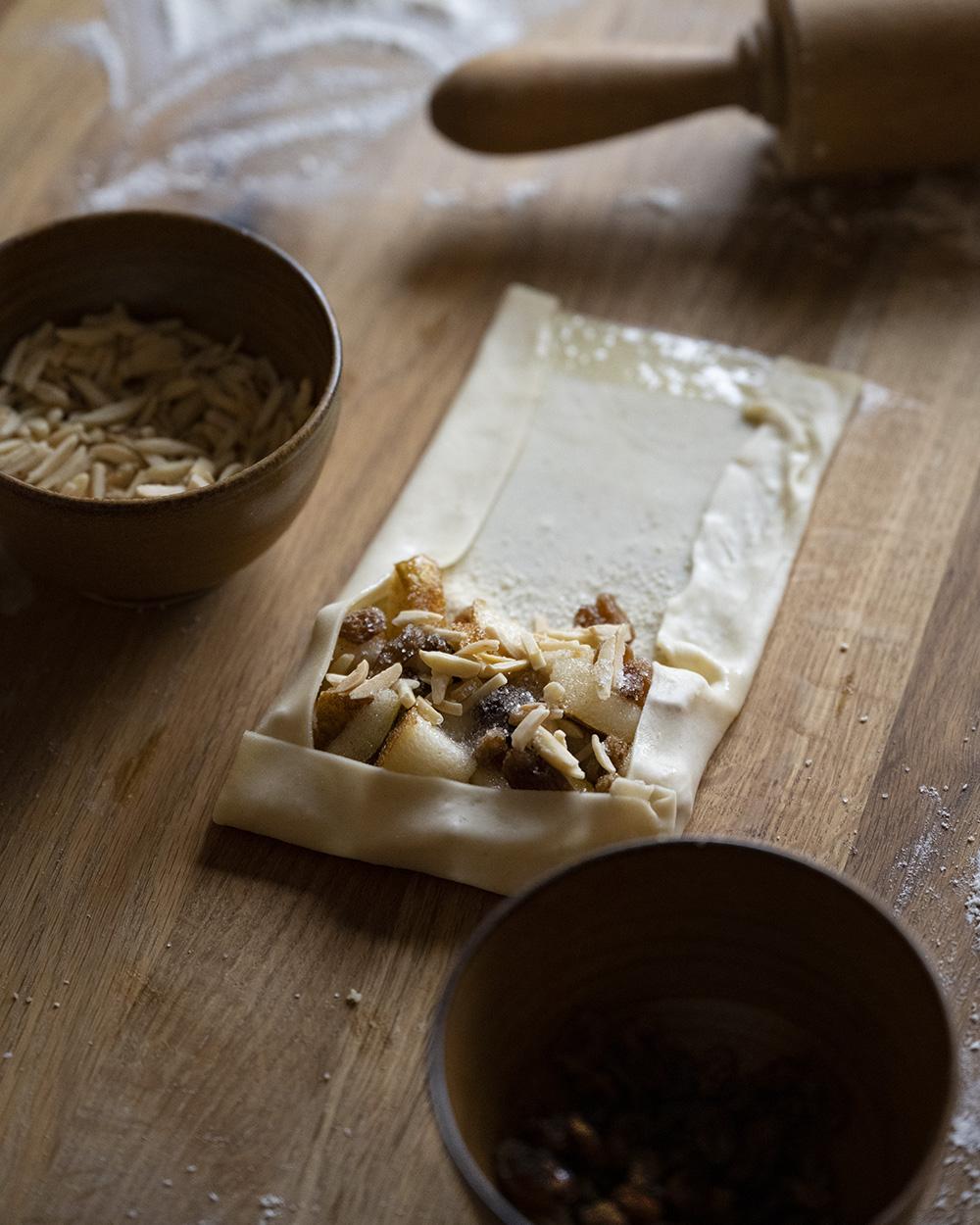 Wir haben die Ränder des Filoteigs mit Butter eingestrichen und wickeln gleich die Füllung, die im Teig liegt, in den Teig ein.
