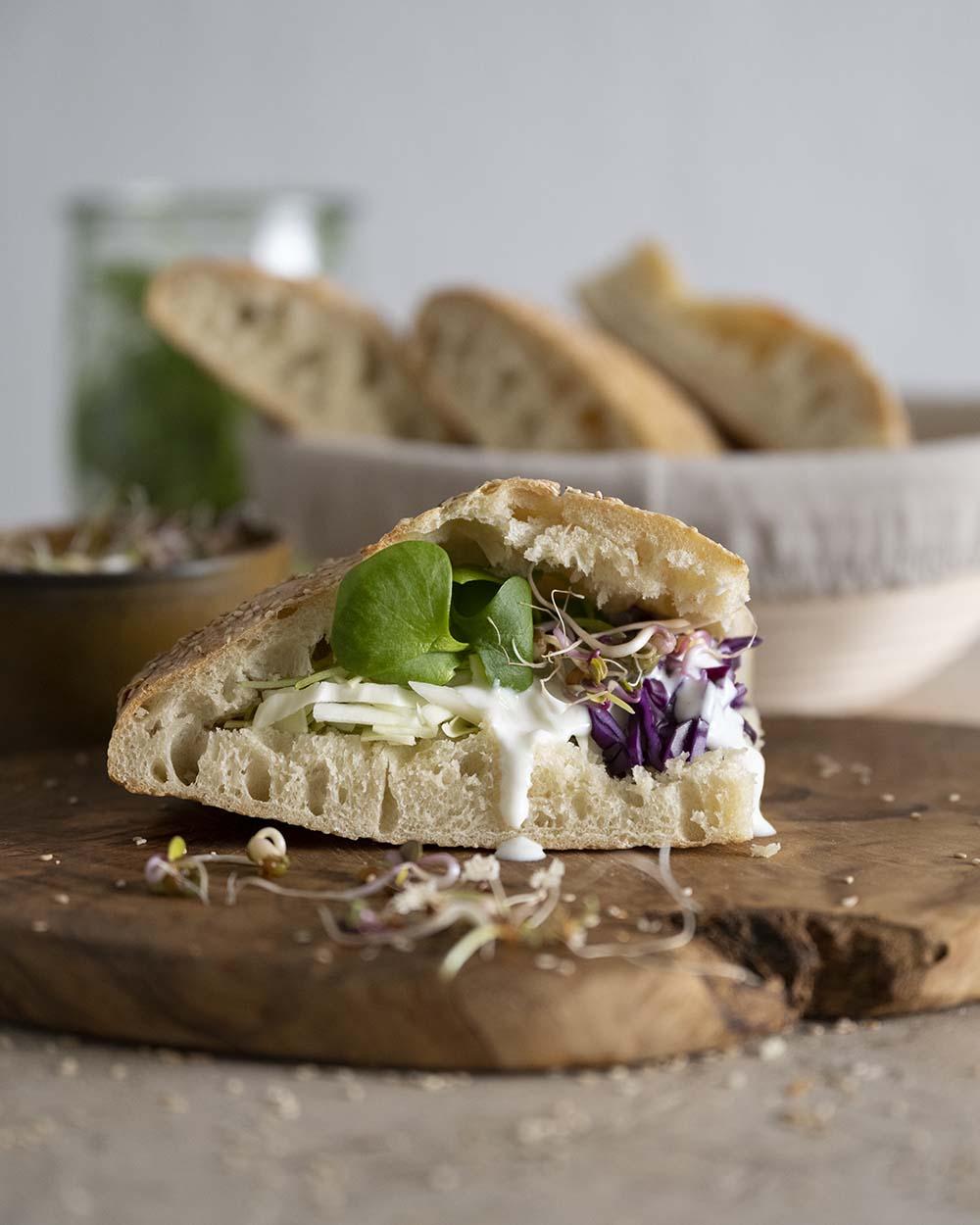 Ein Stück Fladenbrot, befüllt mit einer vegetarischen Füllung aus Salat und Kohl.