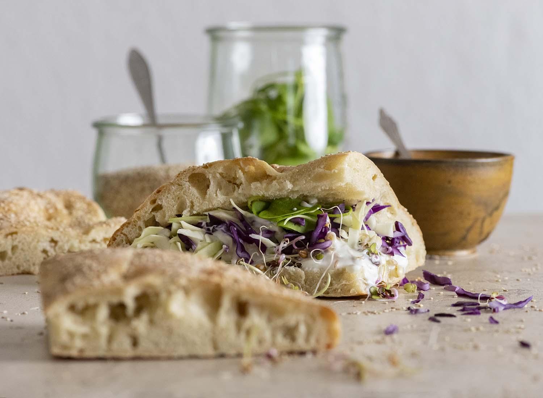 Auf dem Tisch liegt unsere Fladenbrot-Tasche, die wir mit Salat und Kohl gefüllt haben. Im Hintergrund stehen Gläser und Schalen mit den einzelnen Zutaten.
