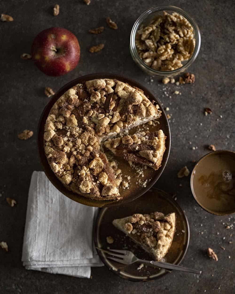 Die Haffeetafel mit dem fertig gebackenen Streuselkuchen, fotografiert von oben. Ein Stück liegt bereits auf einem Teller.