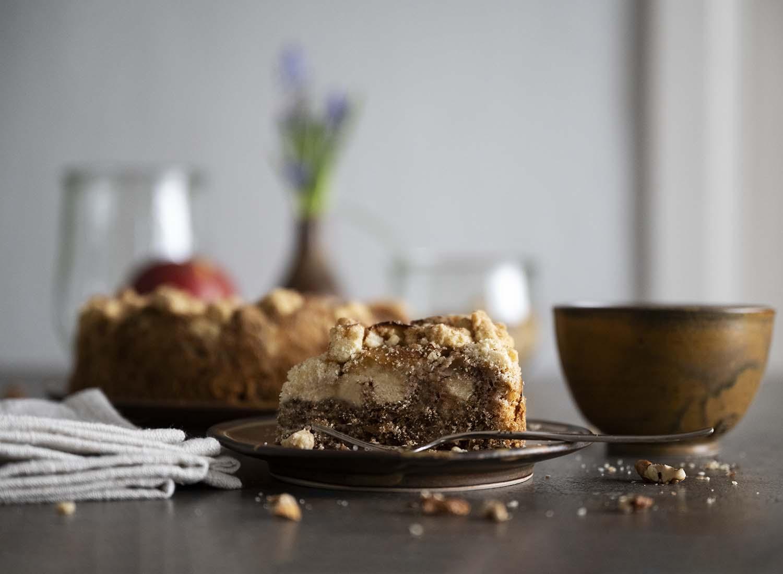 Ein Stück Streuselkuchen auf einem Teller. Zu sehen ist im Anschnitt der Nussboden, auf den wir Äpfel und Streusel geben. Im Hintergrund ist der ganze Streuselkuchen zu sehen.