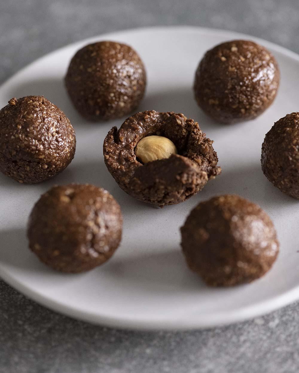 Zu sehen sind mehrere Schoko-Kugeln vor der Glasur mit Schokolade. Eine der Kugeln ist halb offen, damit man die geröstete Haselnuss im Inneren sieht.