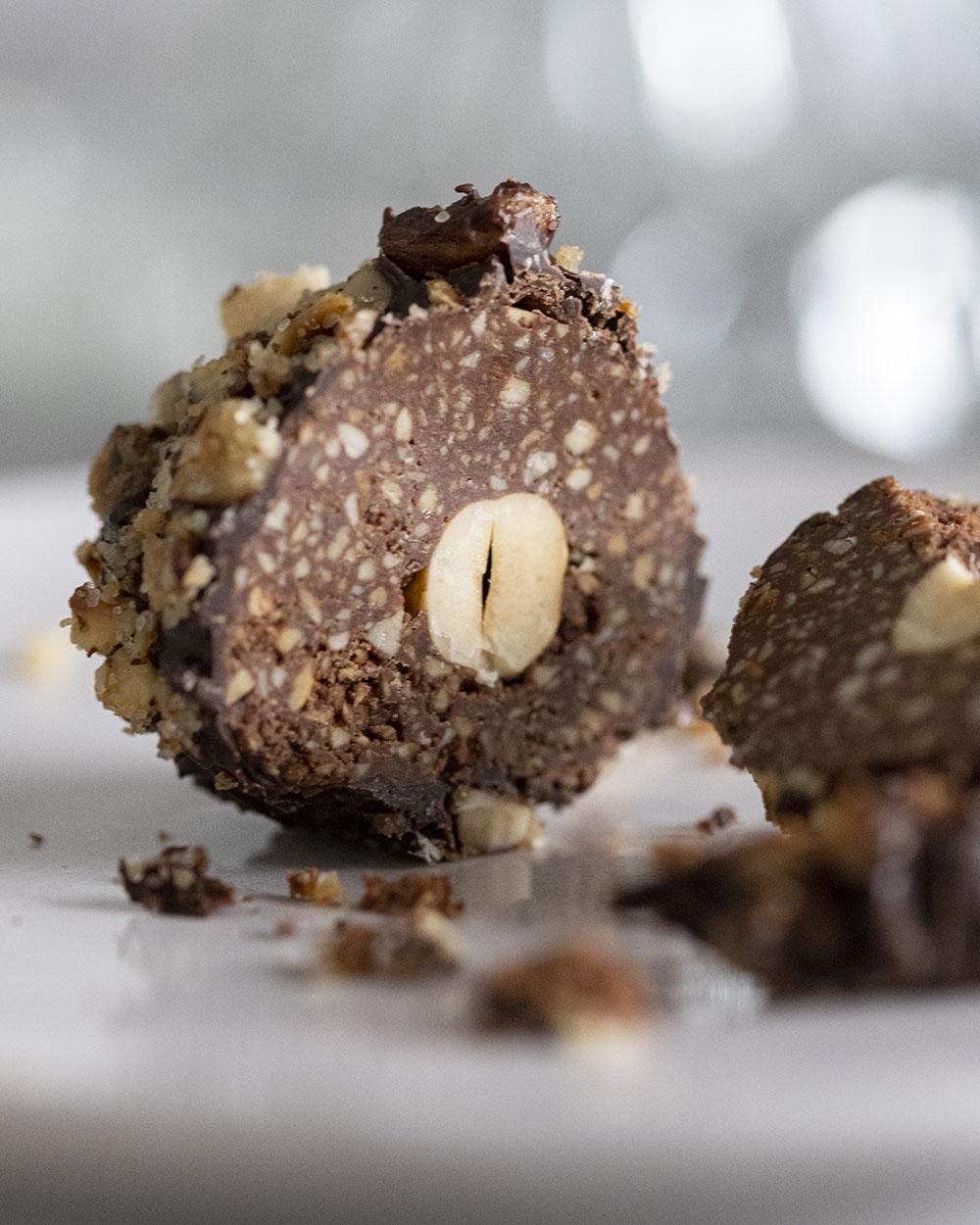 Nahaufnahme einer aufgeschnittenen Schokoladenkugel. Im Inneren ist die ganze Haselnuss zu sehen.