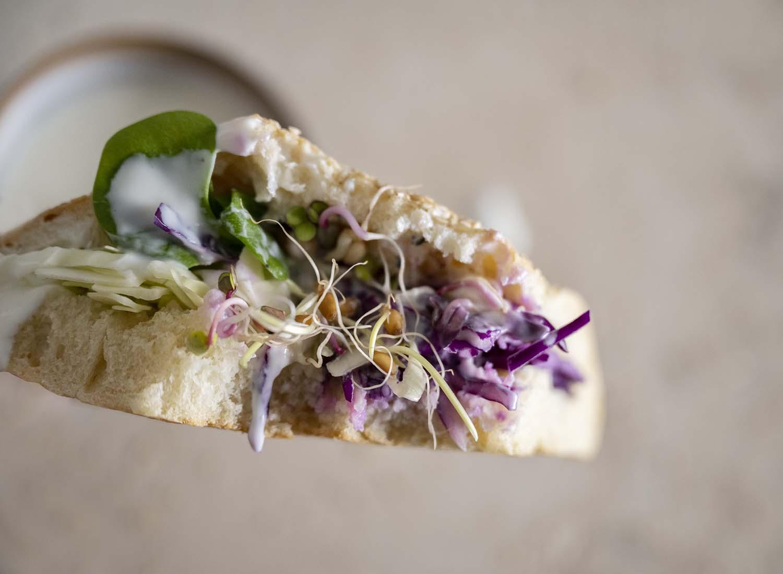 Wir halten ein Stück selbst gemachtes Fladenbrot mit einer vegetarischen Füllung und unserem selbstgemachten Joghurt-Dessing ins Bild.