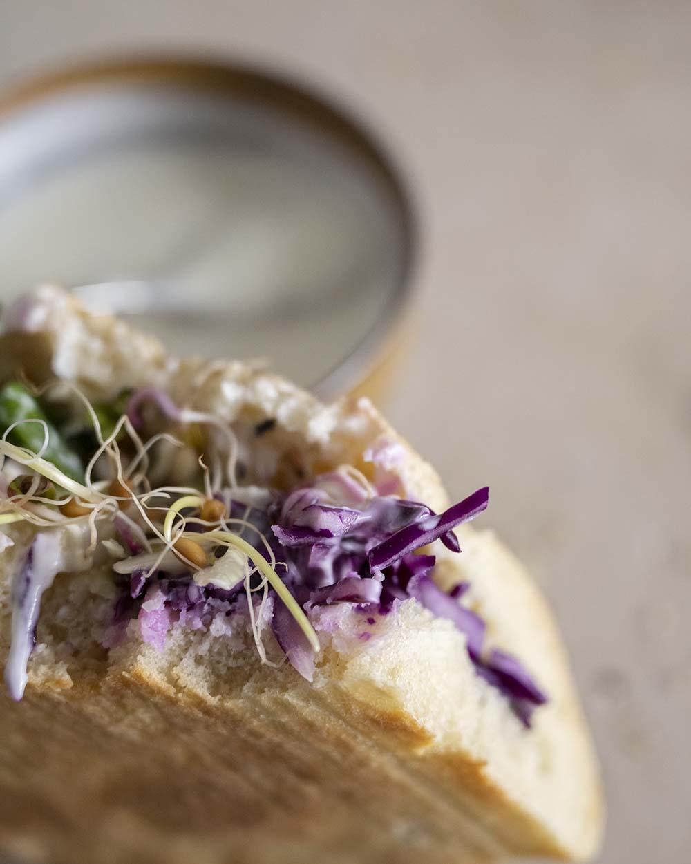 Nahaufnahme unseres vegetarischen Döners. Im Hintergrund ist die Schale mit dem selbst gemachten Joghurt-Dressing zu sehen.