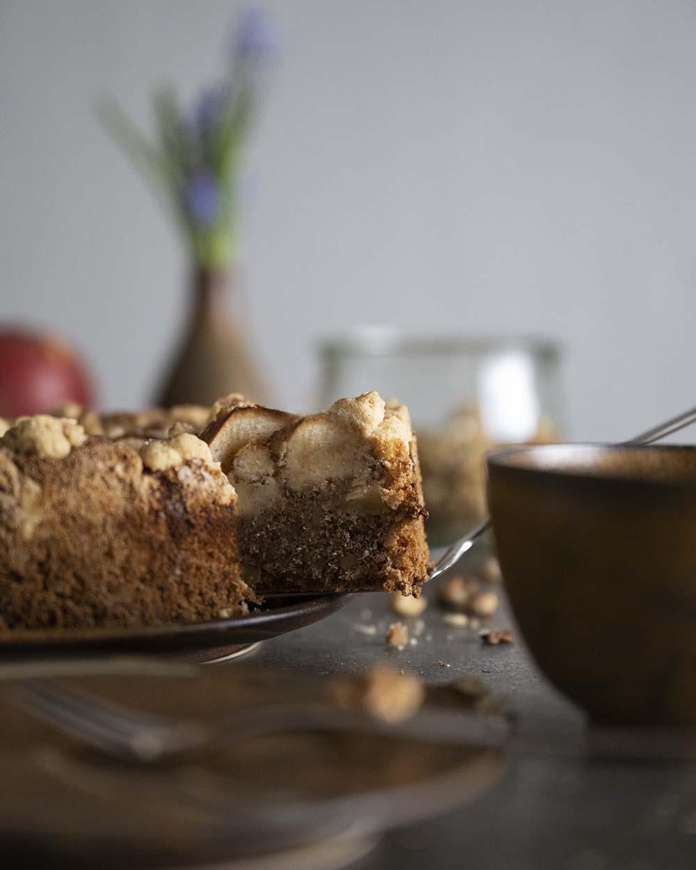 Unseren Streuselkuchen haben wir mit einem Rührteig aus Walnüssen gebacken. Im Anschnitt ist der Boden zu sehen, darauf liegen ganze Äpfel und Streusel.