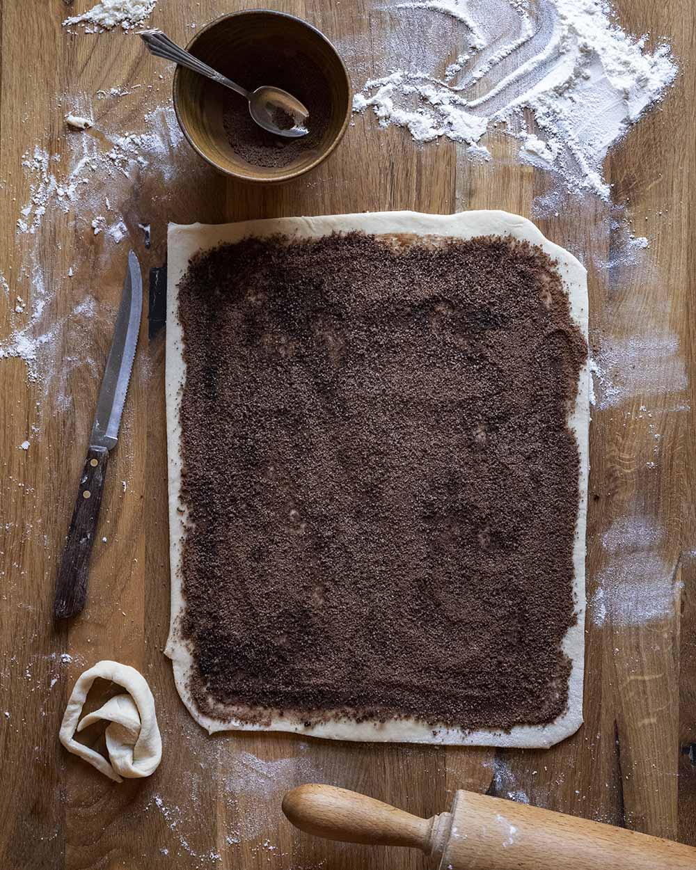 Das erste von mehreren Step-by-Step-Fotos: Wir haben den Teig für unsere Zimtschnecken ausgerollt und mit der Fülung aus Zucker, Zimt und Kakao eingestrichen.