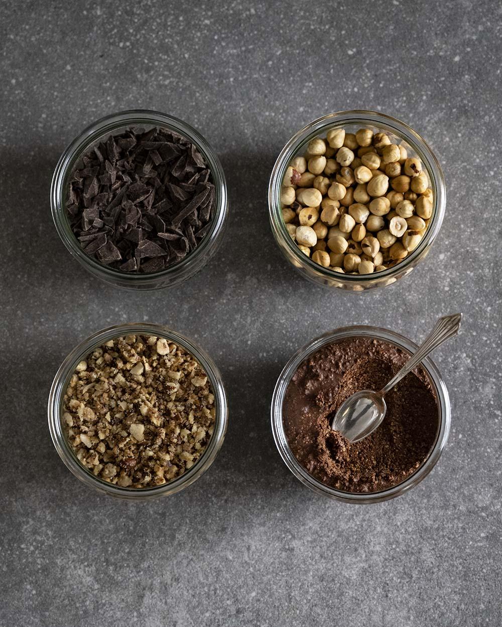 Alle Zutaten für usnere Schoko-Kugeln auf einen Blick und fotografiert von oben: geröstete Haselnüsse, die Schoko-Creme, Krokant und gehackte Schokolade.