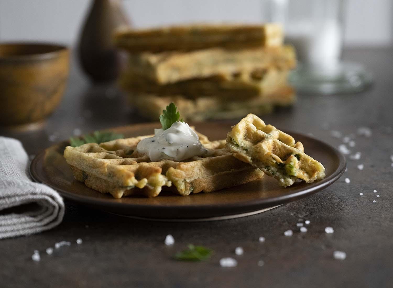 Nahaufnahme einer frischen Kartoffelwaffeln, die wir auf einen Teller gelegt und aufgebrochen haben. Zu sehen sind auch die Kräuter im Teig.