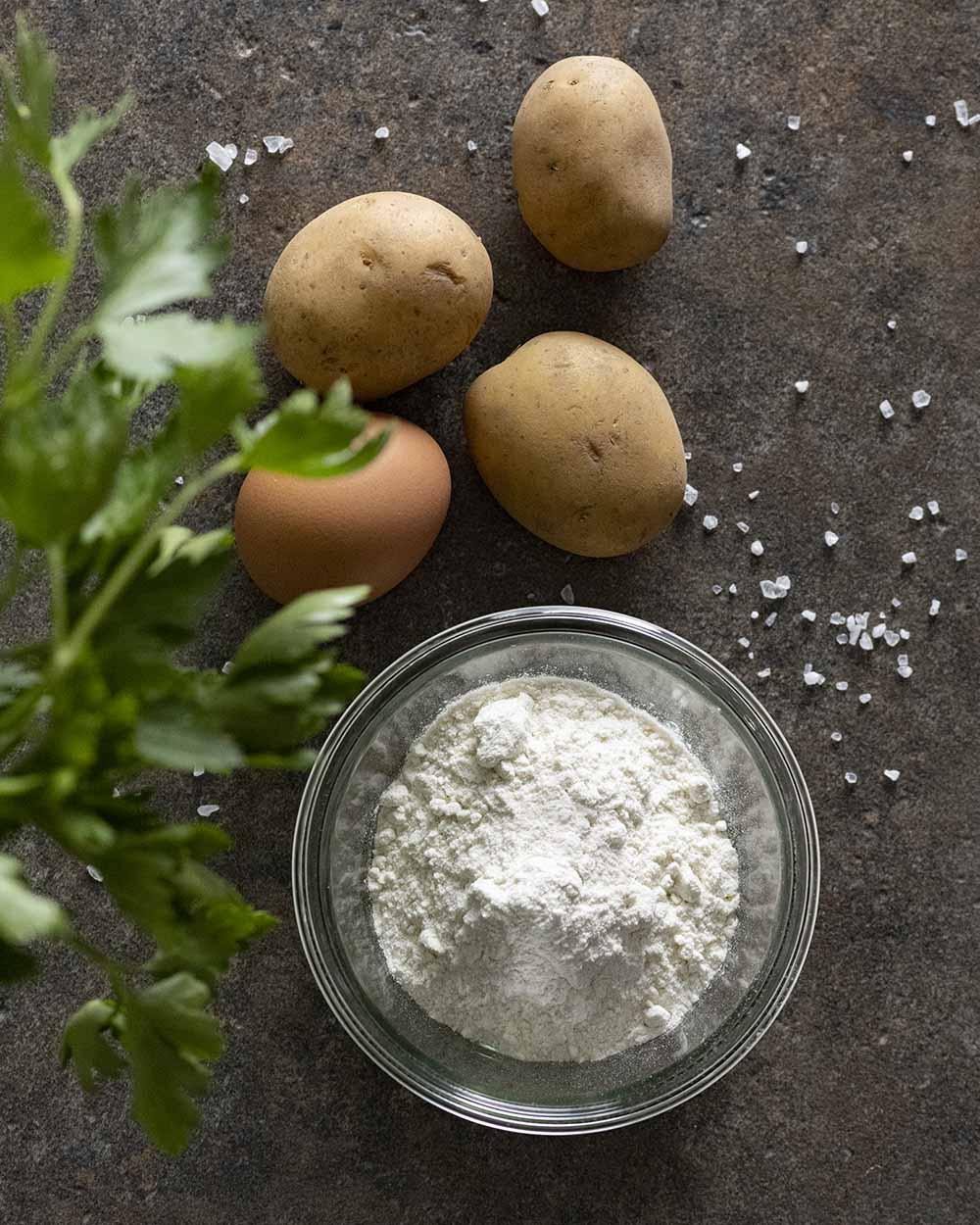 Auf dem Foto sind die Zutaten für unsere selbstgemachten Kartoffelwaffeln zu sehen, darunter frische Petersilie, Kartoffeln, ein Ei und Mehl.
