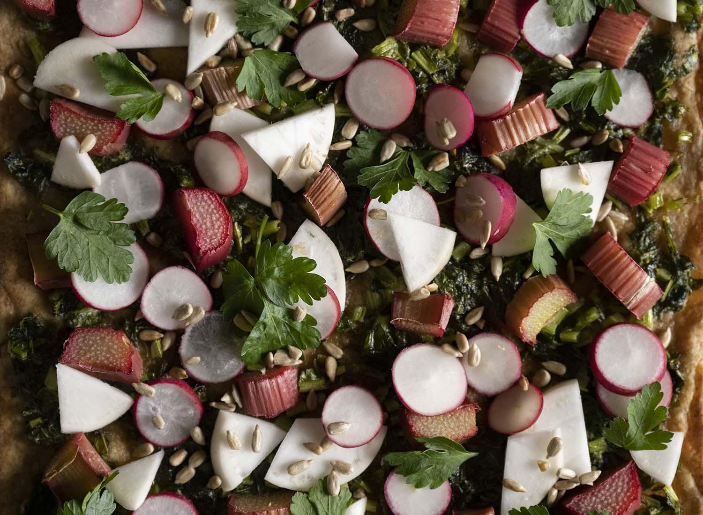 Nahaufnahme des Belags: zu sehen sind Mairübchen, radieschen, glatte Ptersilie, geröstete Sonnenblumenkerne und unser veganer Einstrich aus Blattgrün. Das Rezept für diesen knusprigen Flammkuchen ist vegan.