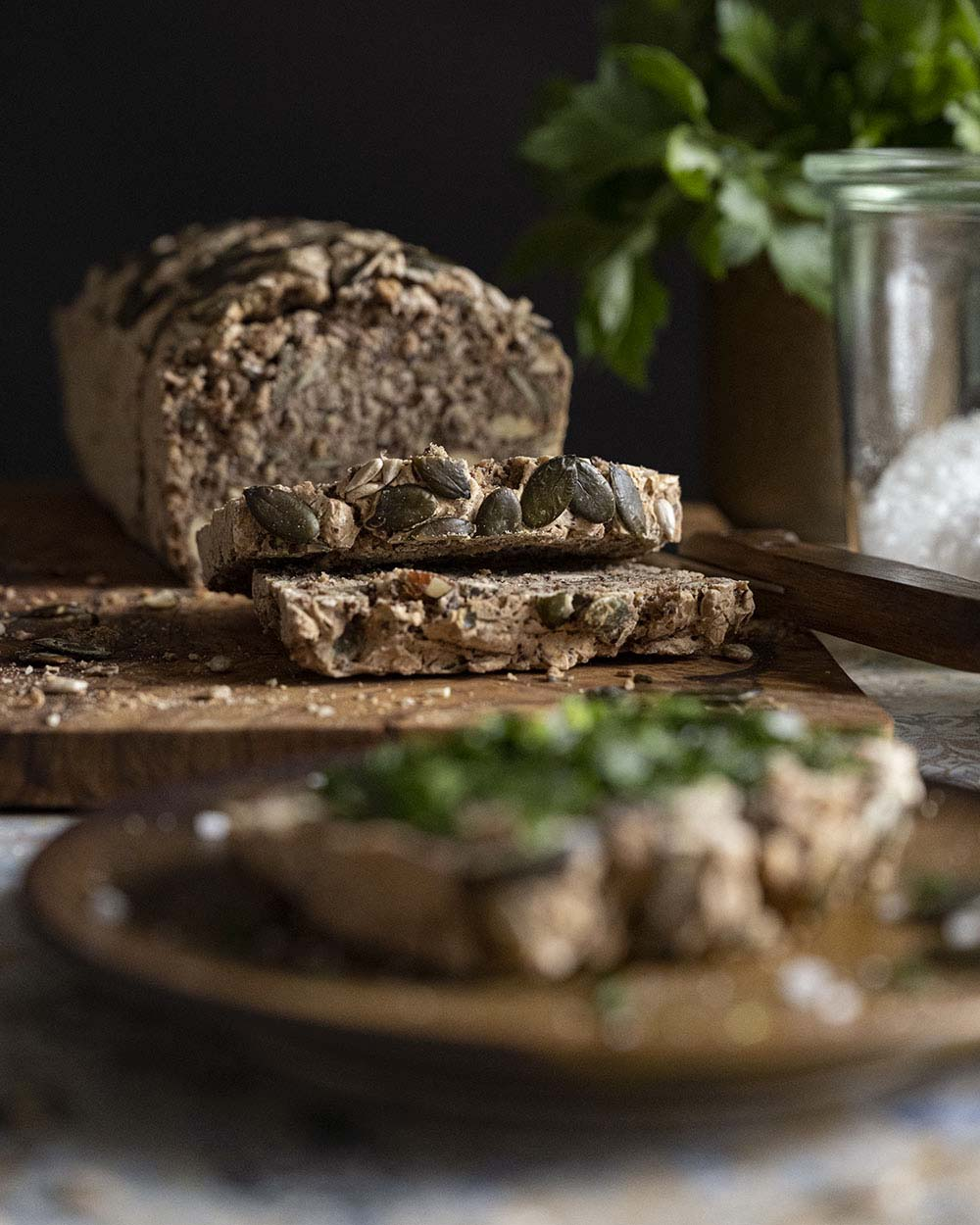 Wir haben den Abendbrottisch eingedeckt. Im Vordergrund ist ein Teller zu sehen, auf dem eine Scheibe Brot liegt. Im Hintergrund ist das ganze Brot zu sehen.