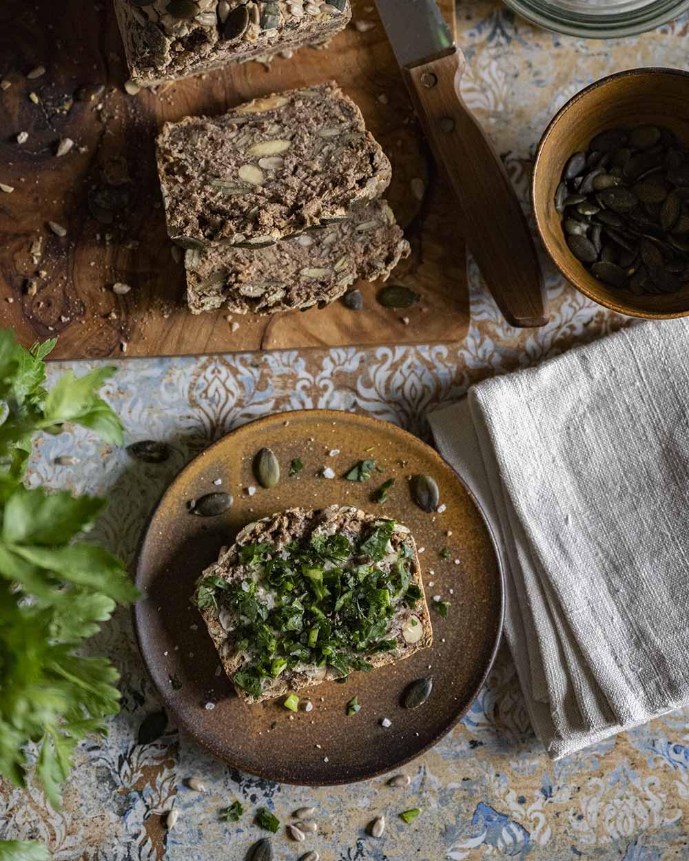 Unser Buchweizenbrot ist vegan und glutenfrei. Hier haben wir den Tisch noch einmal von oben fotografiert. Es zeigt ine Scheibe auf dem Teller, das Brett, uf dem das anze Brt liegt, daneben steht eine Schale mit Kürbiskernen, die auch im Brotteig enthalten sind.