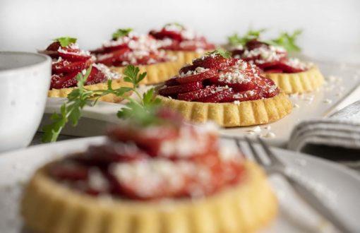 Unsere selbst gemachten Erdbeer Tartelettes sind fertig. Wir haben sie auf der Kaffeetafel agerichtet. Im Vordergrund ist ein Tartelette auf einem Teller zu sehen.