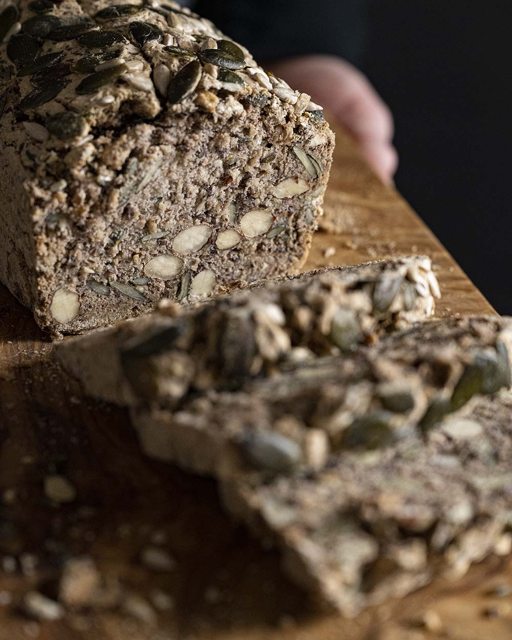 Nachaufnahme unseres angeschnittenen glutenfreien Buchweizenbrots. Ich habe drei Scheiben von ihm abgeschnitten. Zu sehen sind auch die Mandeln im Teig.