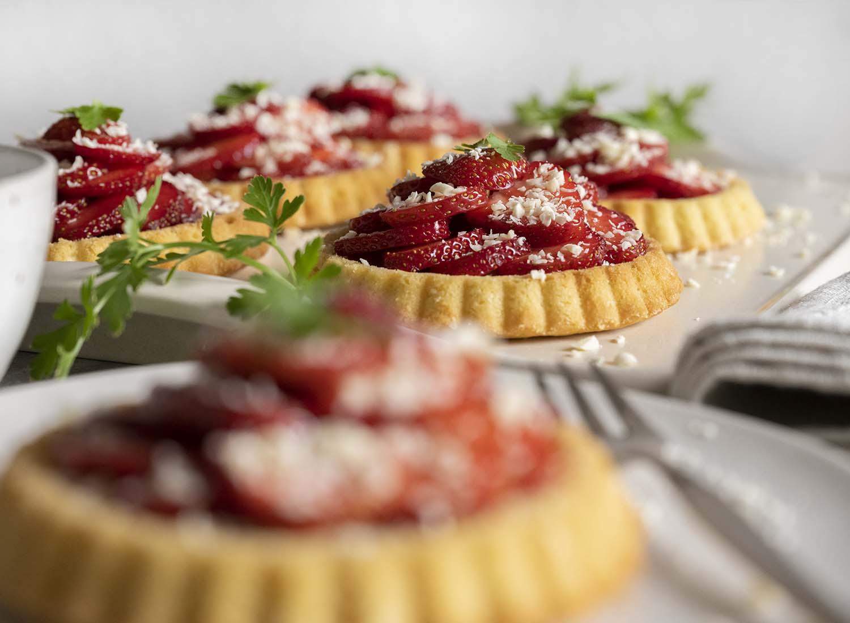 Wi haben unsere frisch gebackenen Erdbeer-Tartelettes auf dem Tisch angerichtet. Im Vorderung ist ein Tartelette auf einem Teller zu sehen. Die übrigen Tartelettes sind auf einer Anrichte-Platte drapiert.