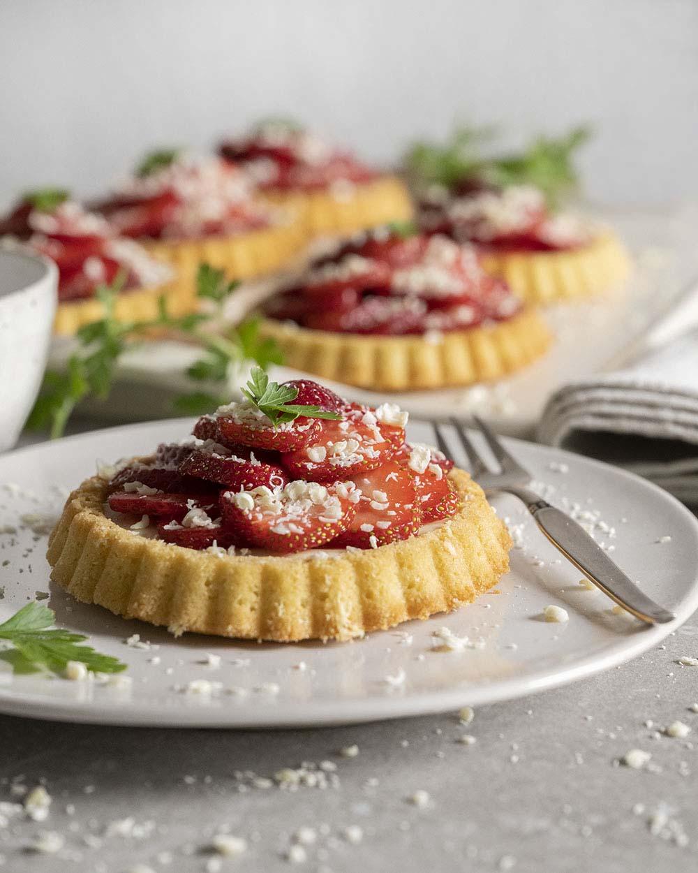 Nahaufnahme eines Erdbeer-Tartelettes, das wir auf einem Teller angerichtet haben. Gleich wollen ir es anschneiden und zeigen, wie die Struktur des Gebäcks im Anschnitt aussieht.