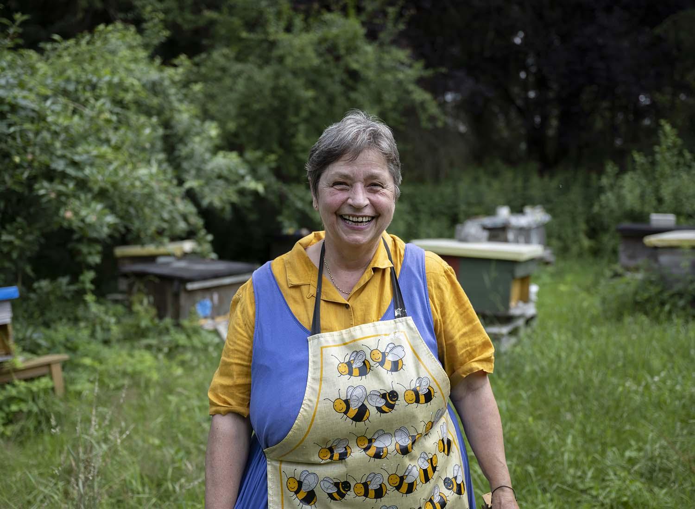 Birgit Wahlen steht im Garten vor den Beuten ihrer Bienen. Neben dem Anbau von Beeren widmet sic Birgit auch der Imkerei.