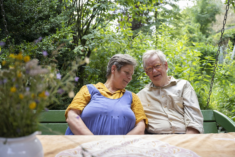 Birgit und Hinrich Wahlen sitzen im Garten ihres Obsthofs.