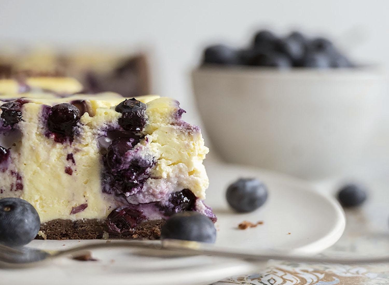 Nahaufnhme der Kuchenspitze unseres Blaubeer-Käsekuchens. Zu sehen ist, wie cremig der Kuchen geworden ist und wie viele Früchte wir in der Creme verarbeitet haben.