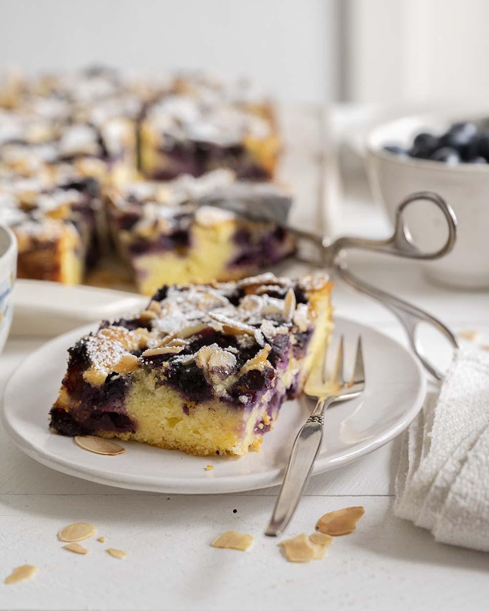 Ein Stück Blechkuchen mit Heidelbeeren auf dem Teller.