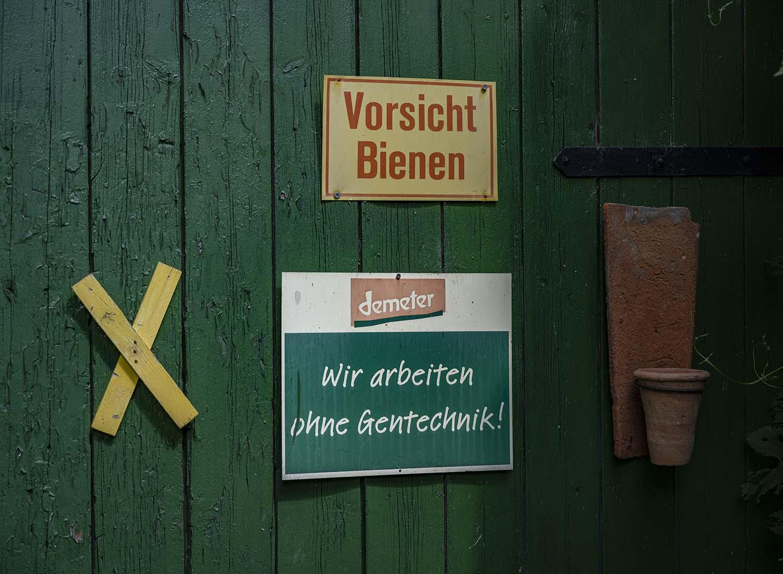 Das Scheunentor auf dem Obsthof Wahlen. Daran hängt ein gelbes Kreus, das ein Symbol für die Demonstrationen gegen die Castor-Transporte ist. Daneben ist das Schild von Demeter angebracht, das ausweist, dass di Wahlens ohne Gentechnik arbeiten.