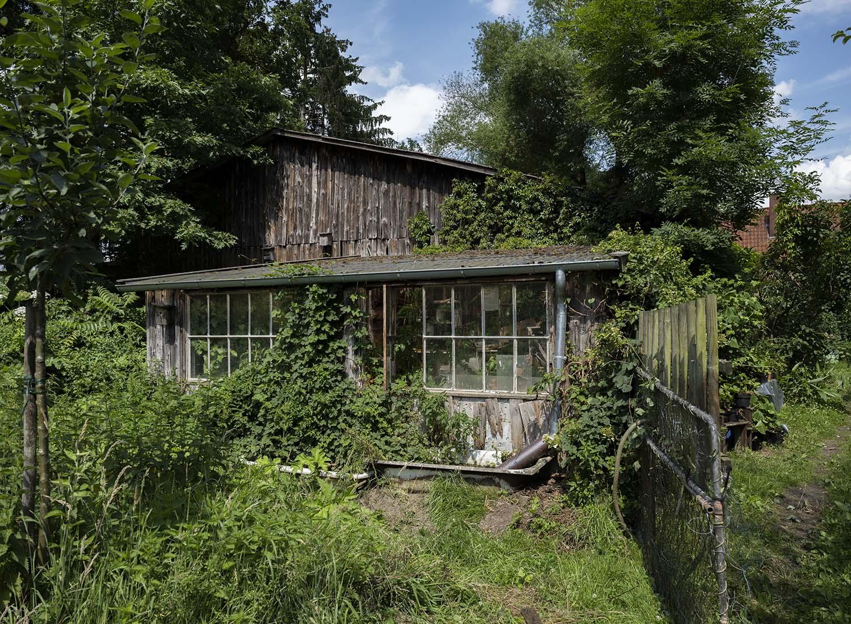 Ansicht des Gartens und des Gewächshauses. Die Bauten auf dem Obsthof Wahlen sind fast alle aus Holz.