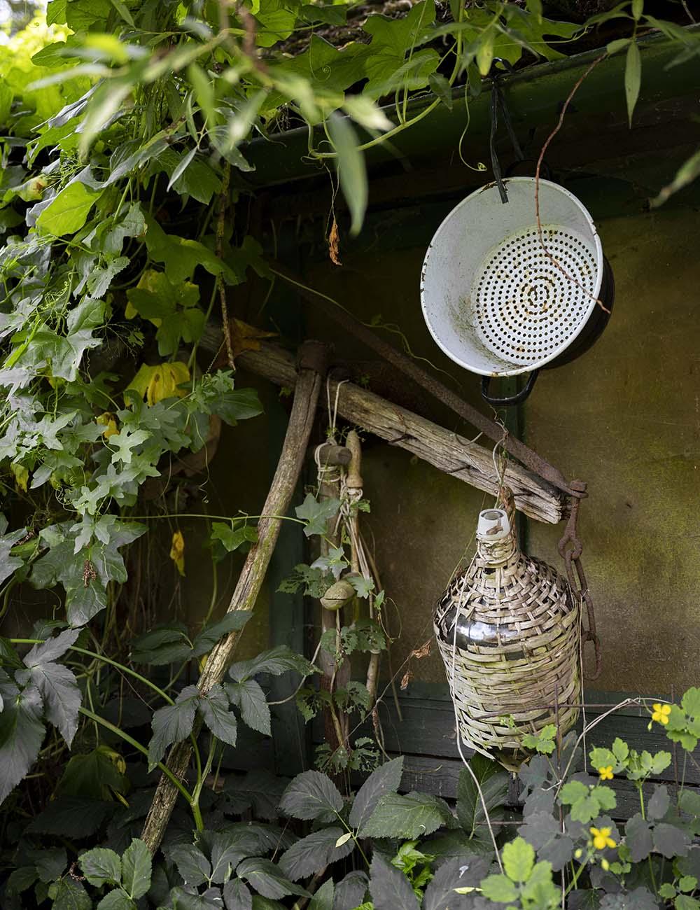Im Garten der Wahlens hängen alte Utensilien unter einem Scheunendach. Zu sehen ist unter anderem eine Emailleschüssel.