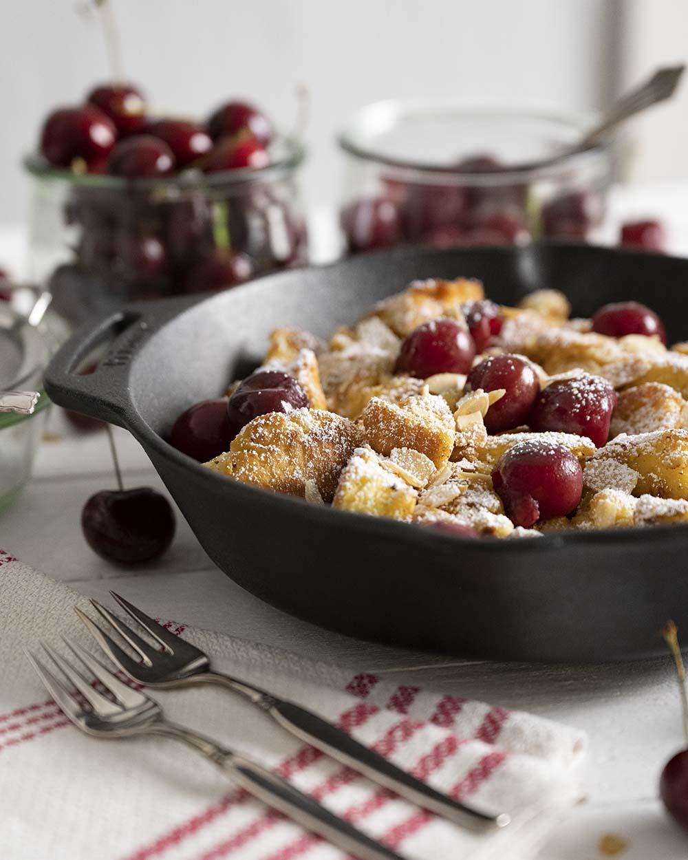 Eine Pfanne mit fertig gebackenem Kaiserschmarrn steht auf dem Tisch. Wir haben das Gericht angerichtet, mit warmen Kirschen, Puderzucker und angerösteten Mandelblättchen.